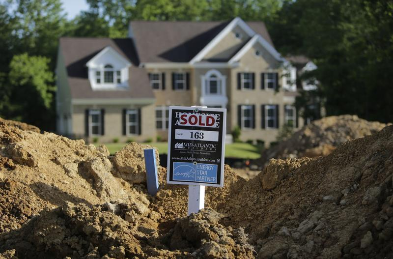 A completed house is seen behind the earthworks of a home currently under construction in Brandywine