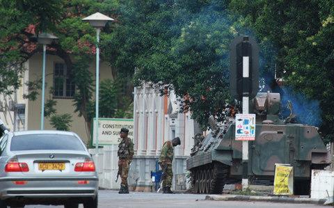 A military tank is seen with armed soldiers on the road leading to President Robert Mugabes office in Harare - Credit: AP