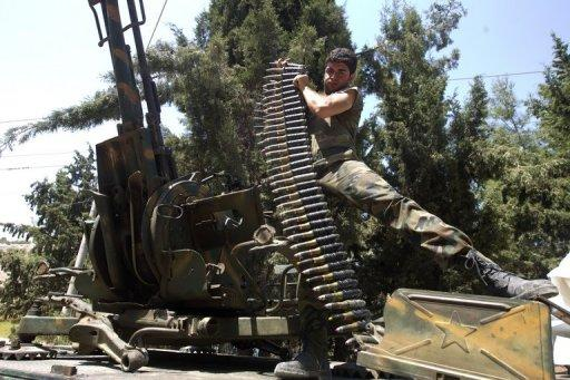 A Syrian rebel fighter loads an anti-aircraft machine gun atop an armoured vehicle in Atareb, 25 kms east of Aleppo, on July 31. Syria's military has used fighter jets to fire on Aleppo, the country's second city, the UN Supervision Mission in Syria (UNSMIS) spokeswoman told AFP on Wednesday