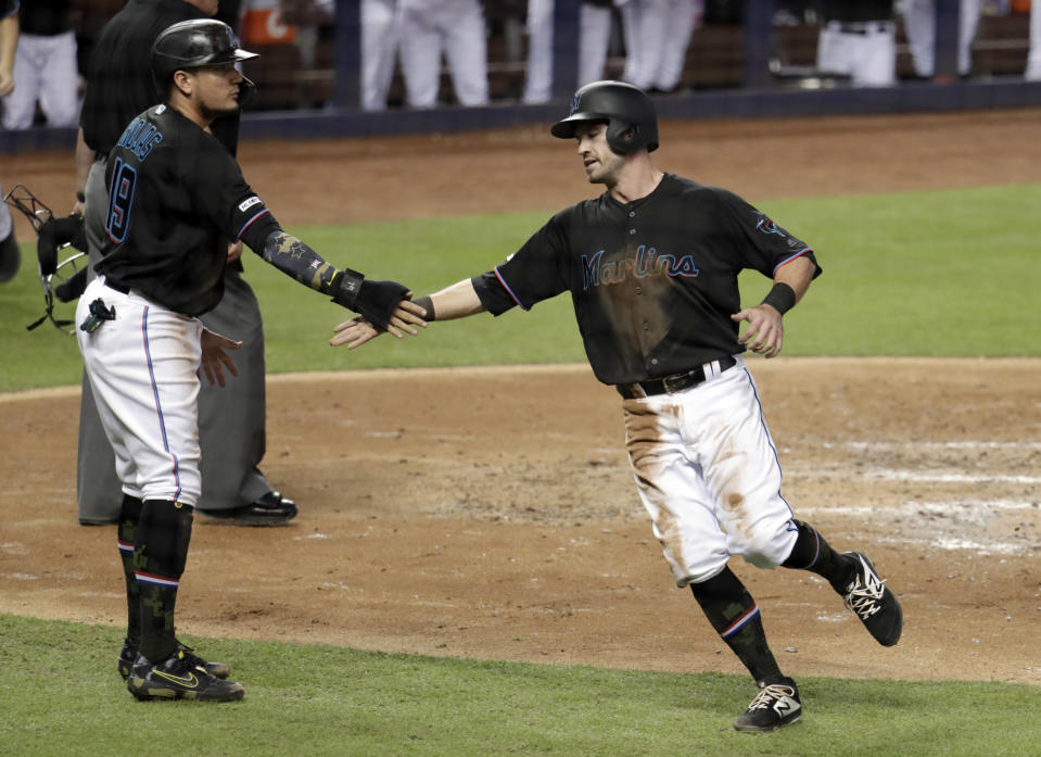 Miami Marlins' Miguel Rojas (19) and Jon Berti congratulate each other after scoring on a single by Garrett Cooper during the third inning of the team's baseball game against the New York Mets, Friday, May 17, 2019, in Miami. (AP Photo/Lynne Sladky)