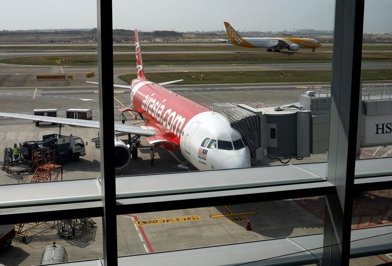 A Scoot airplane takes off past an Airasia airplane at Changi Airport Terminal 4 in Singapore