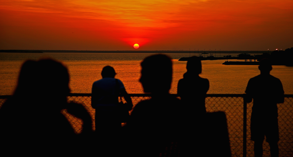 A group of people at a lookout as the sun sets in the NT.