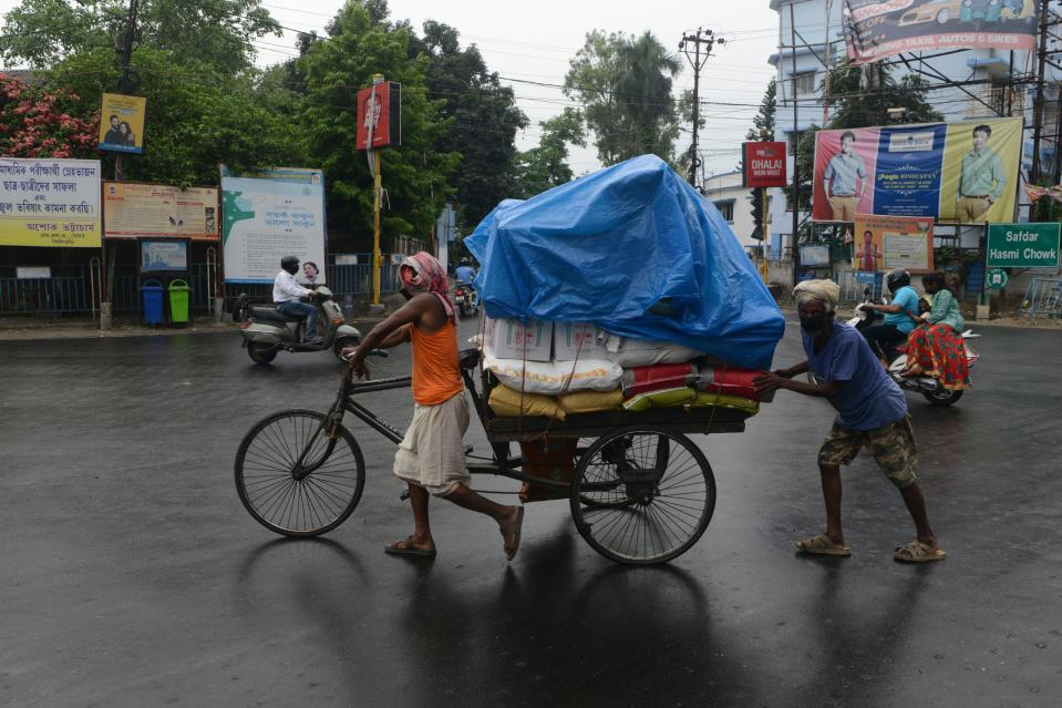 Men push a tricycle cart with a plastic sheet covering the load during a rainfall in Siliguri on May 20, 2020. (Photo by DIPTENDU DUTTA / AFP) (Photo by DIPTENDU DUTTA/AFP via Getty Images)