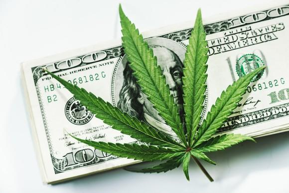 A marijuana leaf on a stack of $100 bills.