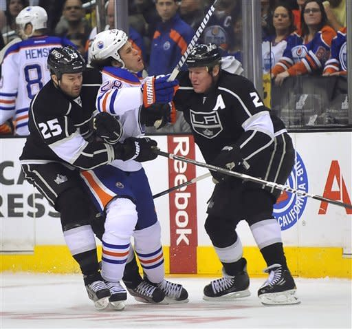 Edmonton Oilers' Ryan Jones, center, is checked between Los Angeles Kings' Dustin Penner, left, and Matt Greene during the first period of an NHL hockey game, Monday, April 2, 2012, in Los Angeles. (AP Photo/Richard Hartog)