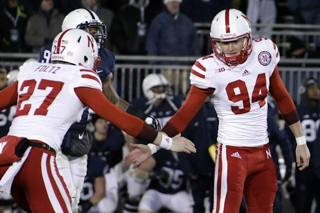 Nebraska kicker Pat Smith (94) celebrates with teammate Sam Foltz (27) after kicking a game-winning field goal to beat Penn State 23-20 in overtime during an NCAA college football game in State College, Pa., Saturday, Nov. 23, 2013. (AP Photo/Gene J. Puskar)