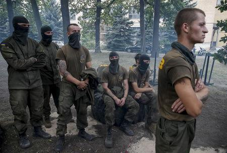 """New volunteers for the Ukrainian interior ministry's """"Azov"""" battalion look on as they take part in tests before heading to frontlines in eastern Ukraine, at the battalion's training centre in Kiev"""