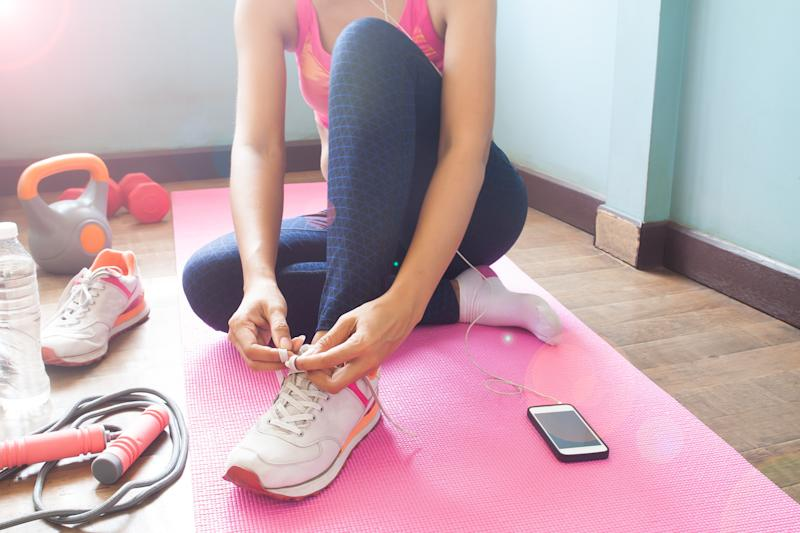 Woman tying her shoelaces on a workout mat from home