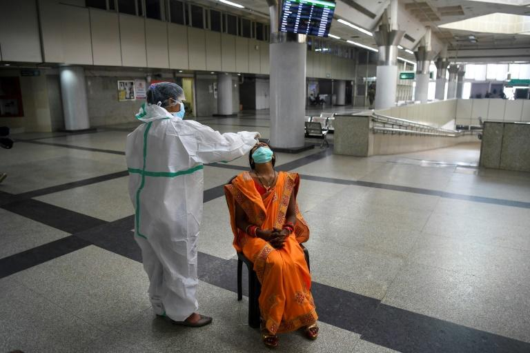A medical worker wearing protective gear collects a swab sample from a passenger at a bus terminal in New Delhi.