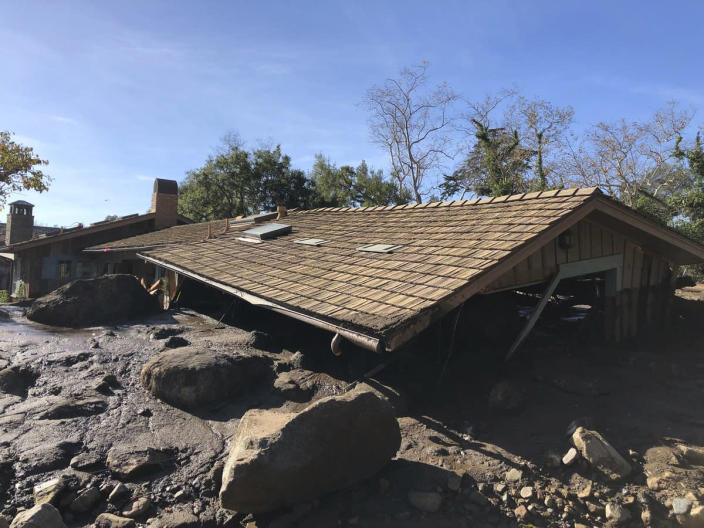 <p>Mudflow, boulders, and debris from heavy rain runoff from early Tuesday reached the roof of a single story home in Montecito, Calif., on Wednesday, Jan. 10, 2018. (Photo: Mike Eliason/Santa Barbara County Fire Department via AP) </p>