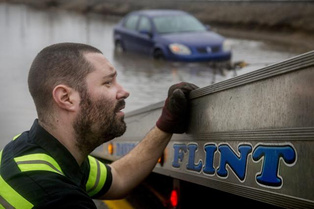 <p>Jeremy Beagle of Burton City Towing watches the cable as he tows a vehicle that was stuck on Robert T. Longway Boulevard on Tuesday, Feb. 20, 2018, in Flint, Mich. High water closed roads in Michigan. (Photo: Bronte Wittpenn/The Flint Journal-MLive.com via AP) </p>