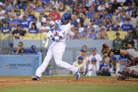 Los Angeles Dodgers' Cody Bellinger, left hits a two-run home run as Arizona Diamondbacks catcher Bryan Holaday watches during the first inning of a baseball game Saturday, July 10, 2021, in Los Angeles. (AP Photo/Mark J. Terrill)