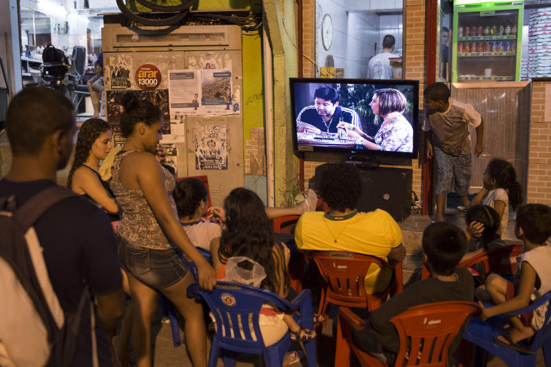 """People watch the final chapter of the soap opera Avenida Brasil in a small outdoor plaza in the Dona Marta slum in Rio de Janeiro, Brazil, Friday, Oct. 19, 2012. """"Telenovelas,"""" prime-time soap operas with average runs of 200 episodes, are hugely popular in Brazil, where the plot lines often become front page news and where discussions of the heroes and villains are a major topic of conversation. (AP Photo/Felipe Dana)"""