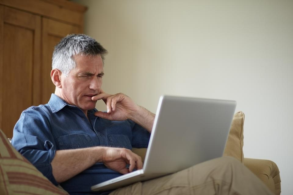 A man sits on a couch looking at his laptop. Lottery agents provide information on past winning numbers.