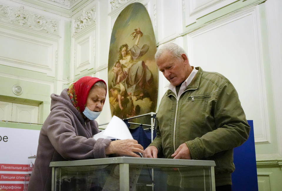 People cast their ballots during the State Duma, the Lower House of the Russian Parliament and local parliaments elections at a polling station situated in an old palace in St. Petersburg, Russia, Saturday, Sept. 18, 2021. Sunday will be the last of three days voting for a new parliament, but there seems to be no expectation that United Russia, the party devoted to President Vladimir Putin, will lose its dominance in the State Duma. (AP Photo/Dmitri Lovetsky)