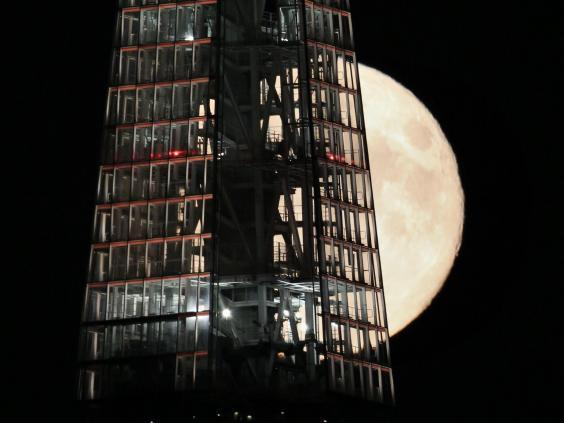 A full moon passes behind The Shard skyscraper on 9 September, 2014 in London, England (Getty Images)