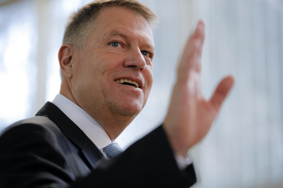 Romanian President Klaus Iohannis waves after casting his vote in Bucharest, Romania, Sunday, Nov. 10, 2019. Voting got underway in Romania's presidential election after a lackluster campaign overshadowed by a political crisis which saw a minority government installed just a few days ago. (AP Photo/Vadim Ghirda)