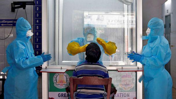PHOTO: A doctor in a protective chamber takes a swab from a man to test for coronavirus disease (COVID-19) at a newly installed Walk-In Sample Kiosk (WISK) in a government-run hospital in Chennai, India, April 13, 2020. (P. Ravikumar/Reuters)