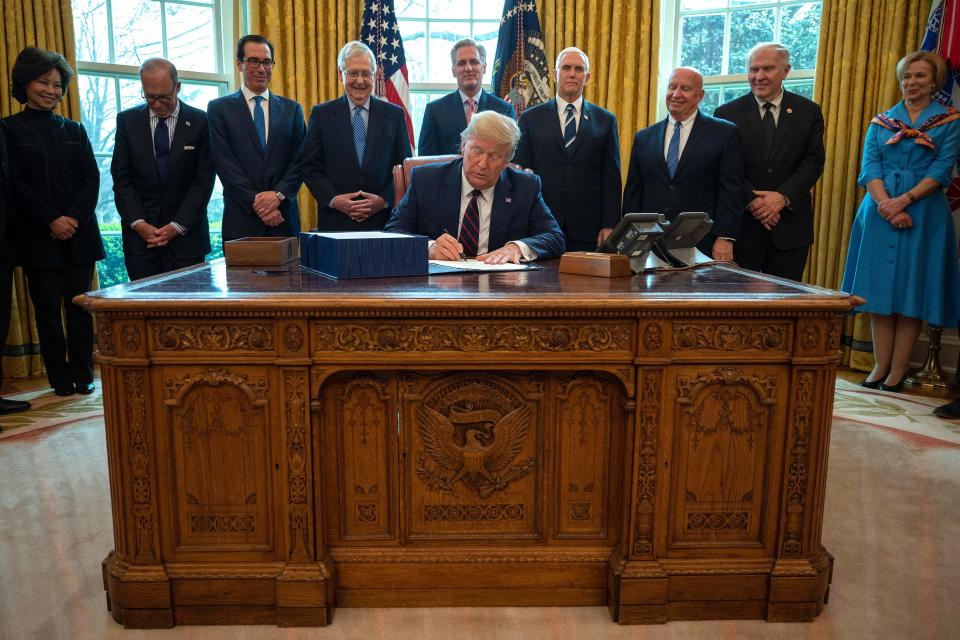 President Trump signs the CARES act, a $2 trillion rescue package to provide economic relief amid the coronavirus outbreak on March 27. (JIM WATSON/AFP via Getty Images)