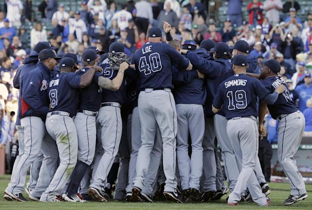 Atlanta Braves players and coaches celebrate after the Braves defeated the Chicago Cubs 5-2 in a baseball game in Chicago, Sunday, Sept. 22, 2013. The Braves clinched the NL East as the Washington Nationals lose to the Florida Marlins. (AP Photo/Nam Y. Huh)