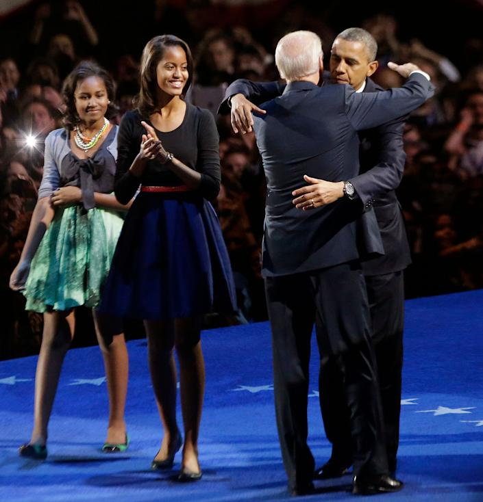 President Barack Obama hugs Vice President Joe Biden as his daughter Malia and Sasha look on at his election night party Wednesday, Nov. 7, 2012, in Chicago. President Obama defeated Republican challenger former Massachusetts Gov. Mitt Romney. (AP Photo/Charles Rex Arbogast)