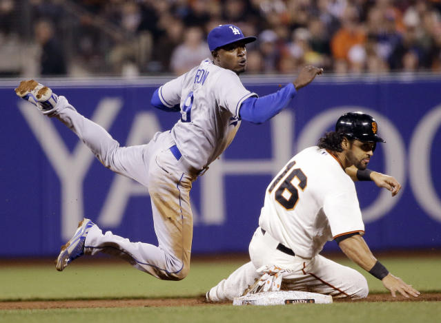 Los Angeles Dodgers second baseman Dee Gordon, left, looks to first after forcing out San Francisco Giants' Angel Pagan (16) at second base on a ground ball from Hunter Pence during the third inning of a baseball game on Wednesday, April 16, 2014, in San Francisco. Pence was safe at first. (AP Photo/Marcio Jose Sanchez)