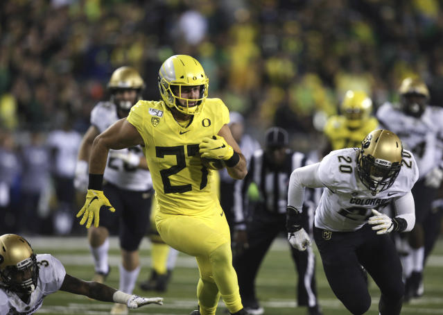 Oregon's Jacob Breeland center, runs for extra yards after a pass reception against Colorado's Derrion Rakestraw, left, and Davion Taylor, right, during the first quarter of an NCAA college football game Friday, Oct. 11, 2019, in Eugene, Ore. (AP Photo/Chris Pietsch)
