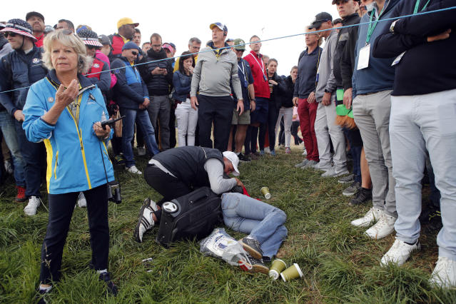 FILE - In this Friday, Sept. 28, 2018 file photo a man tends an unidentified injured woman after she was hit by US player Brooks Koepka's ball on the 6th hole during a fourball match on the opening day of the 42nd Ryder Cup at Le Golf National in Saint-Quentin-en-Yvelines, outside Paris, France. Ryder Cup organizers say they are alarmed by the news that a spectator hit by a Brooks Koepka's tee shot at the Ryder Cup says she has lost sight in her right eye. (AP Photo/Francois Mori, File)