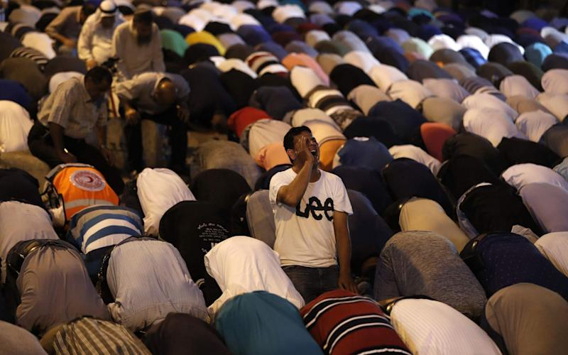 Palestinian Muslim worshippers pray outside al-Aqsa's Lions' Gate in Jerusalem - Credit: AFP