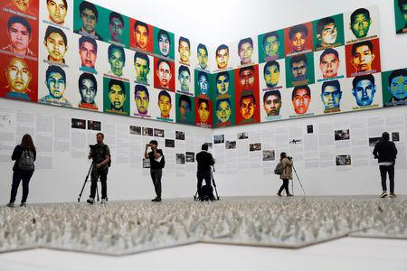 """Journalists are seen in front of portraits of the 43 missing Ayotzinapa College Raul Isidro Burgos students during a press preview of the exhibition """"Restablecer Memorias"""" by Chinese artist Ai Weiwei, displayed at the University Museum of Contemporary Art (MUAC) in Mexico City, Mexico, April 11, 2019. REUTERS/Edgard Garrido/Files"""