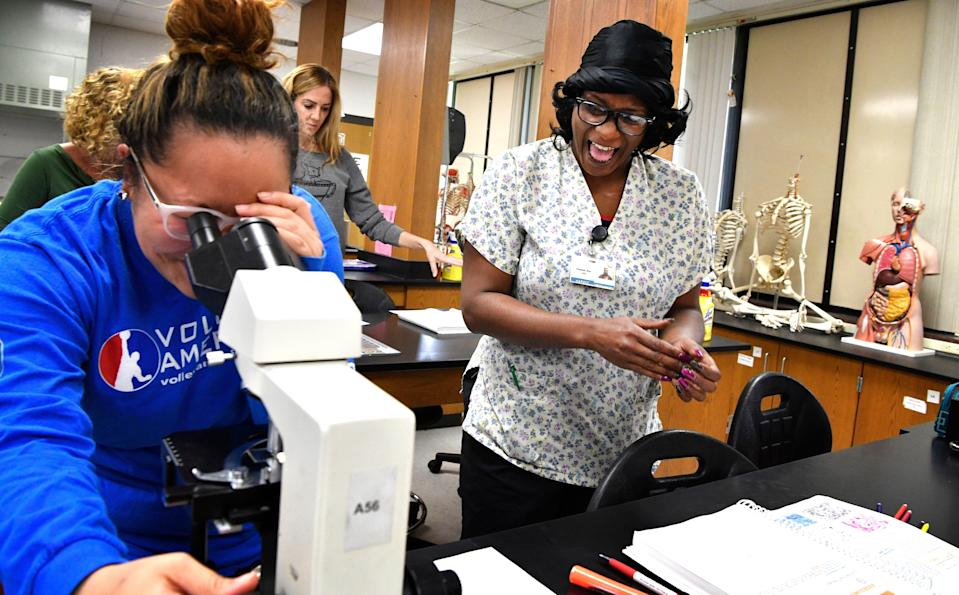 Sheeteah Blair looks on with fellow student as they examine tissue samples during a 2018 anatomy class at Nashville State. Blair used the free Tennessee Reconnect program to pursue a nursing degree.