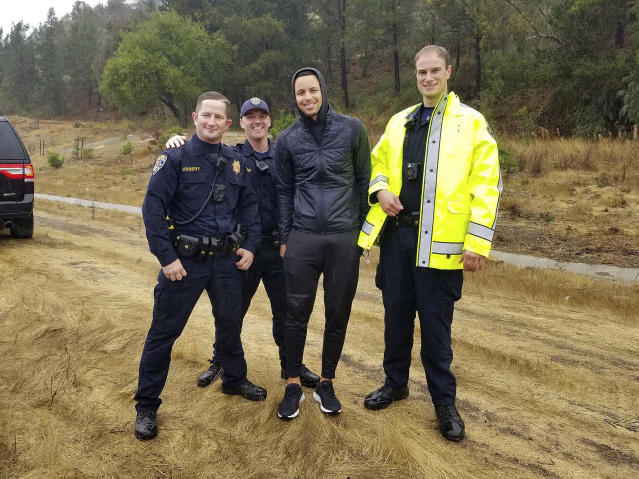 """<a class=""""link rapid-noclick-resp"""" href=""""/nba/players/4612/"""" data-ylk=""""slk:Stephen Curry"""">Stephen Curry</a>, shown with California Highway Patrol officers, was not injured in a car crash last week. (California Highway Patrol Oakland via AP)"""