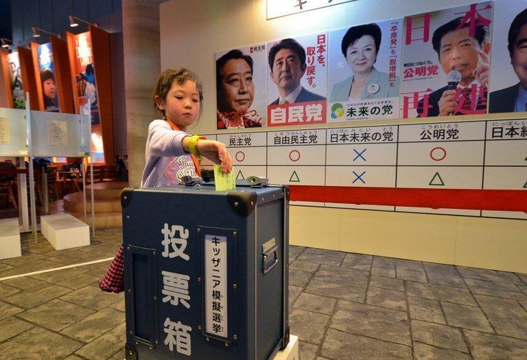 A little girl casts a mock vote in a straw poll at the Kidzania career theme park in Tokyo on December 14, 2012