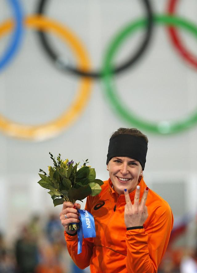 Ireen Wust of the Netherlands flashes three fingers indicating her third olympic gold medal, during the flower ceremony after winning gold in the women's 3,000-meter speedskating race at the Adler Arena Skating Center during the 2014 Winter Olympics, Sunday, Feb. 9, 2014, in Sochi, Russia. (AP Photo/Pavel Golovkin)