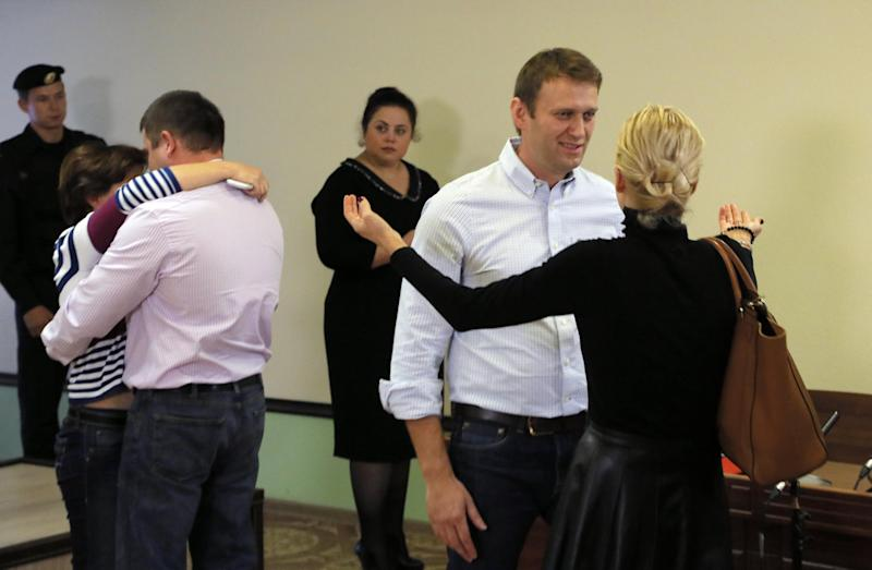 Russian opposition leader Alexei Navalny, second right, his wife Yulia, and his former colleague Pyotr Ofitserov, back to camera, and Offitserov's wife react at the end of a hearing in a court room at a Kirov court in Kirov, Russia, Wednesday, Oct. 16, 2013. The judge of a Russian court has overturned a sentence for opposition leader and anti-corruption blogger Alexei Navalny, handing him a suspended sentence instead of five years in prison. (AP Photo/Dmitry Lovetsky)