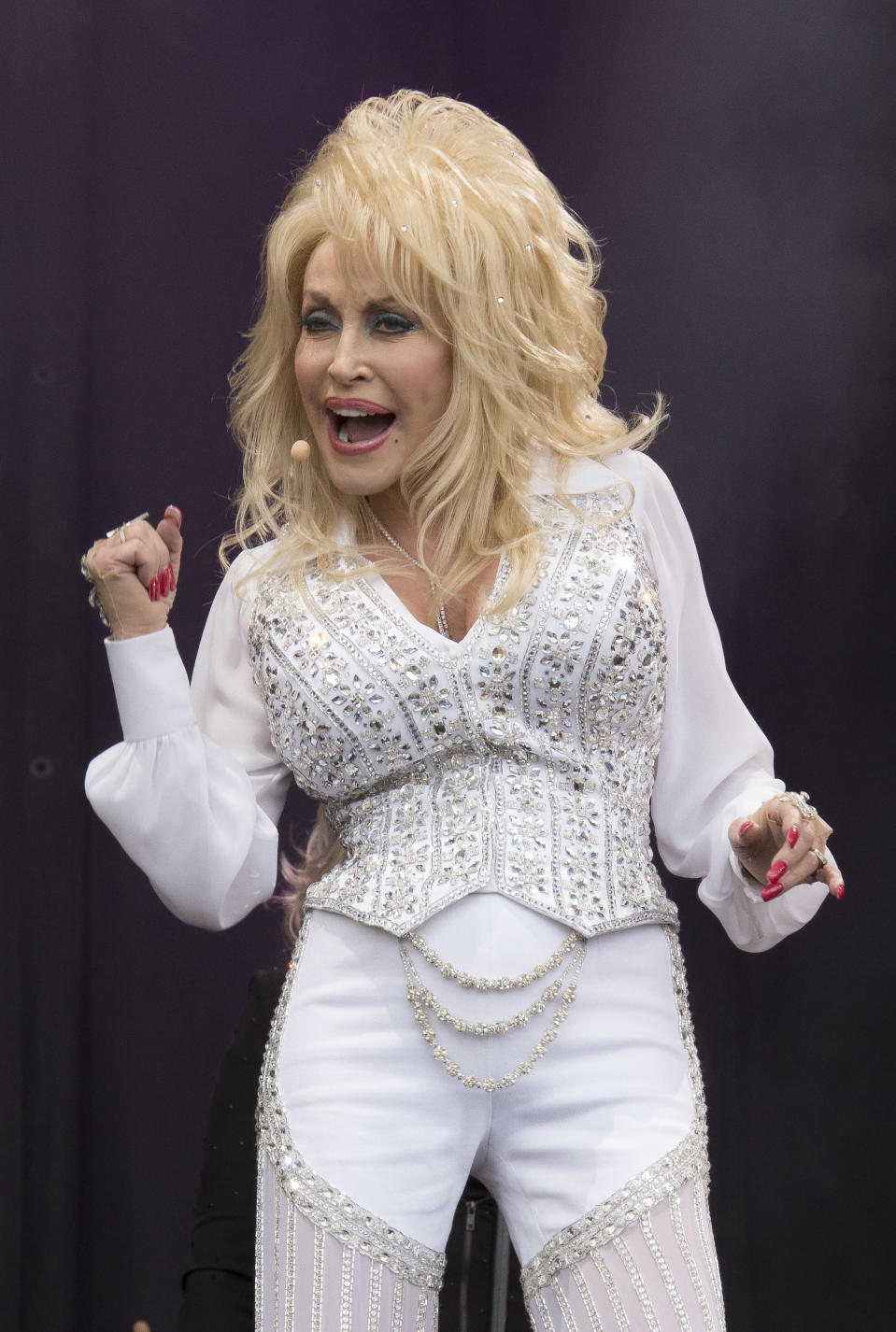 FILE - Dolly Parton performs on the main Pyramid stage at Glastonbury music festival, England on June 29, 2014.It's been 51 years since Dolly Parton earned her first Grammy nomination, and this year the national treasure who has won nine Grammys throughout her career is competing for her 50th honor. (Photo by Joel Ryan/Invision/AP, File)