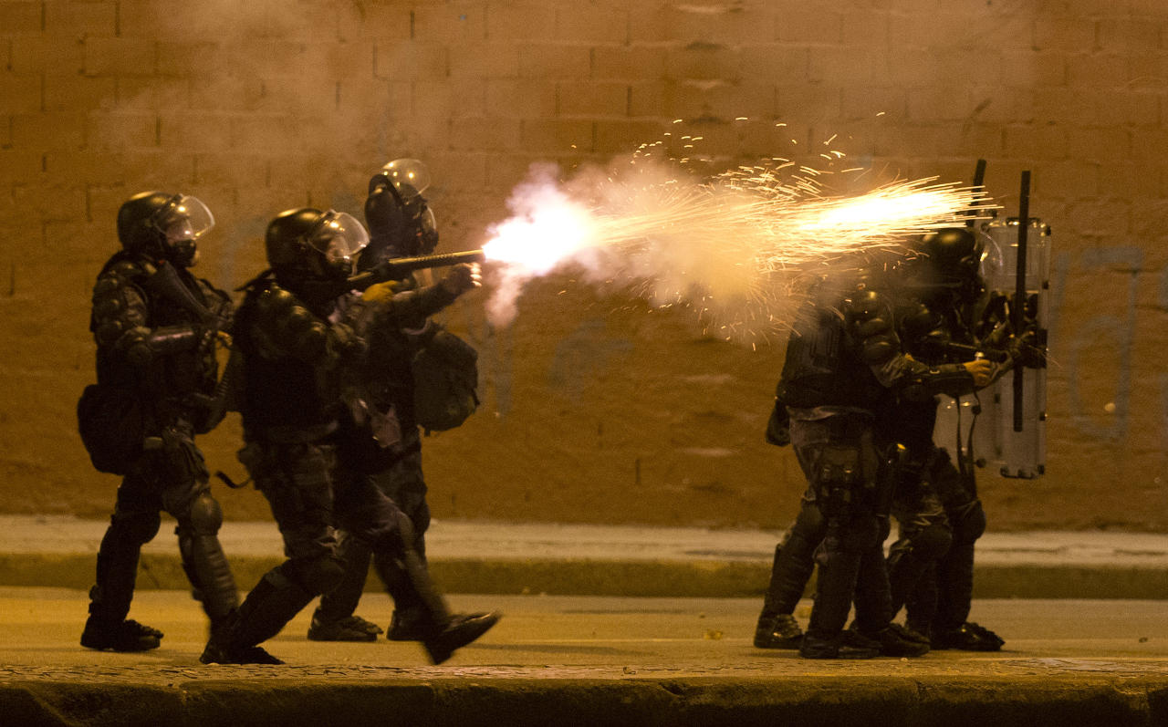 Military police fire tear gas at protestors during an anti-government demonstration in Rio de Janeiro, Brazil, Thursday, June 20, 2013. Police and protesters fought in the streets into the early hours Friday in the biggest demonstrations yet against a government viewed as corrupt at all levels and unresponsive to its people. (AP Photo/Victor R. Caivano)