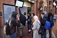 A group of migrants check a departure board at Copenhagen Central Station, Denmark, in this November 12, 2015 file photo. REUTERS/Asger Ladefoged/Scanpix Denmark/Files