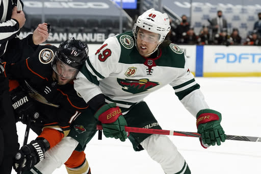 Anaheim Ducks center Adam Henrique (14) faces off against Minnesota Wild center Victor Rask (49) during the first period of an NHL hockey game Monday, Jan. 18, 2021, in Anaheim, Calif. (AP Photo/Marcio Jose Sanchez)