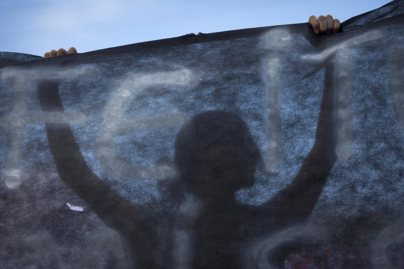 A woman holds up a black banner as people protest near the Kiss nightclub where a fire killed over 230 people in Santa Maria, Brazil, Tuesday, Jan. 29, 2013. The Rio Grande do Sul state forensics department raised the death toll Tuesday from 231 to 234 to account for three victims who did not appear on the original list of the dead. Authorities say more than 120 people remain hospitalized for smoke inhalation and burns, with dozens of them in critical condition, after the Sunday nightclub fire. (AP Photo/Felipe Dana)