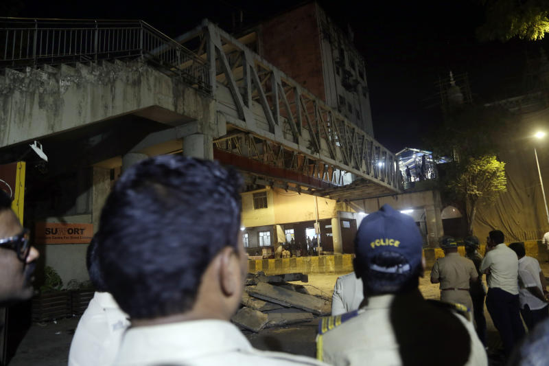 Policemen and others gather near a pedestrian bridge that collapsed in Mumbai, India, Thursday, March 14, 2019. A pedestrian bridge connecting a train station with a road collapsed in Mumbai on Thursday, killing at least five people and injuring more than 30, police said. (AP Photo/Rajanish Kakade)