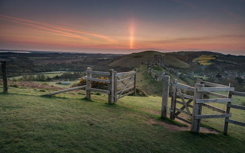 A light pillar is formed by the rising sun over, Corfe Castle, Dorset. - Daniel Sands / SWNS.com
