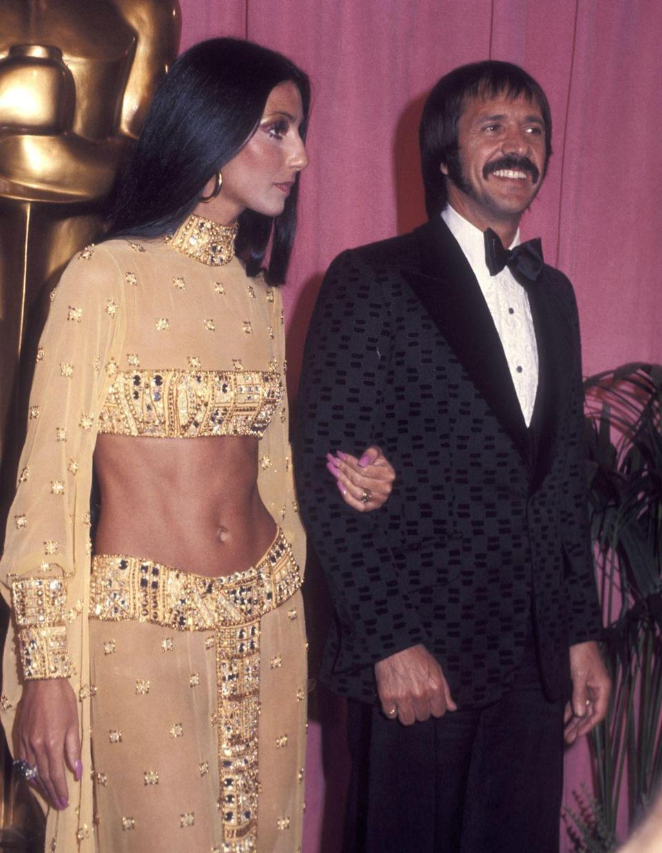 <p>In a sparkling gold two-piece set and hoop earrings at the 45th Annual Academy Awards alongside Sonny Bono. </p>