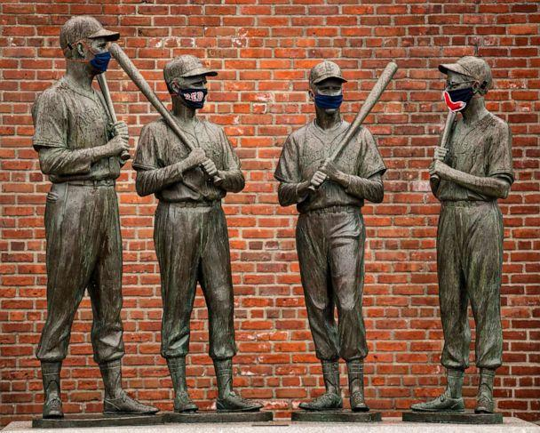 PHOTO: Statues of former Boston Red Sox players Ted Williams, Bobby Doerr, Johnny Pesky and Dom DiMaggio have been decorated with makeshift masks as the Major League Baseball season is postponed, April 9, 2020, at Fenway Park in Boston. (Billie Weiss/Boston Red Sox via Getty Images)