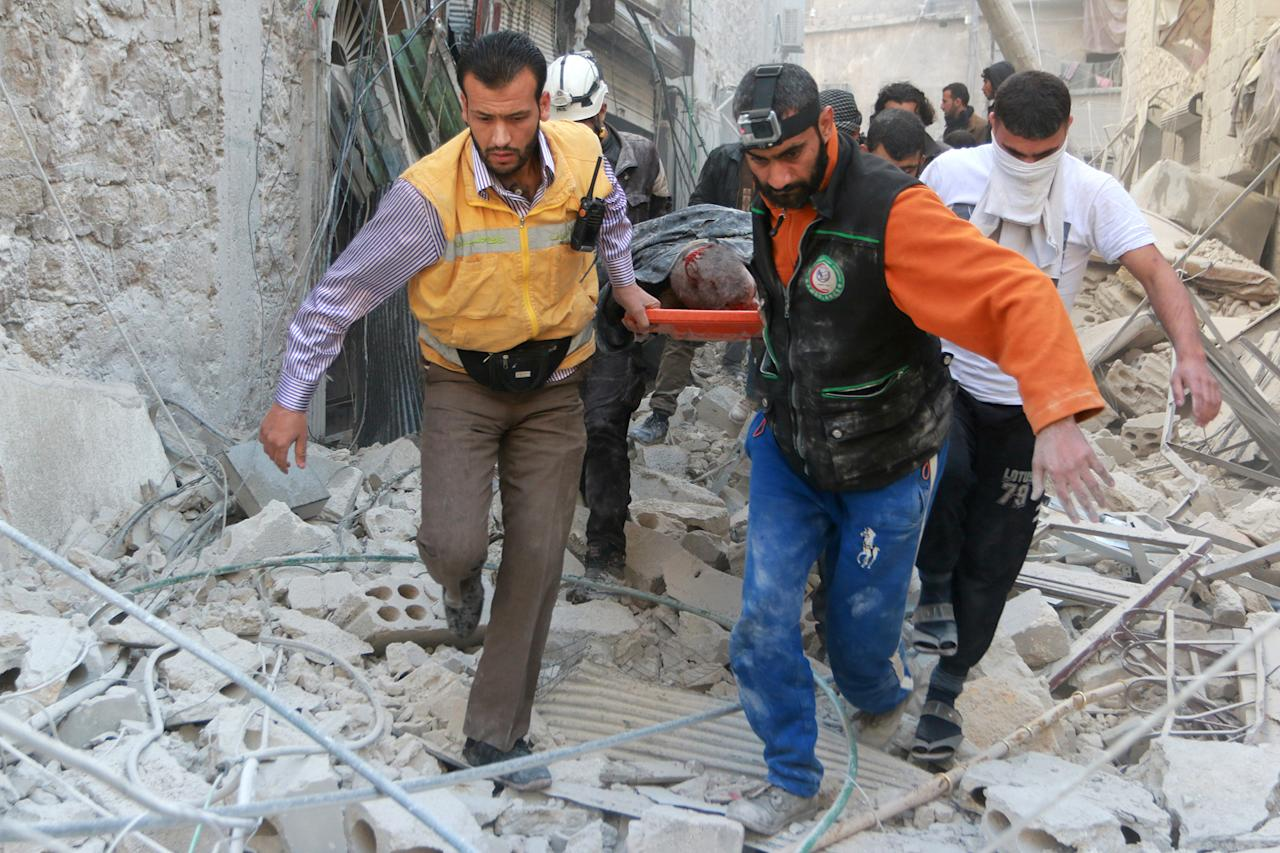 <p>Civil defense team members carry a wounded man on the debris buildings after the war crafts belonging to the Assad Regime carried out airstrikes on residential areas at Firdevs neighborhood in Aleppo, Syria on Nov. 18, 2016. (Jawad al Rifai/Anadolu Agency/Getty Images) </p>