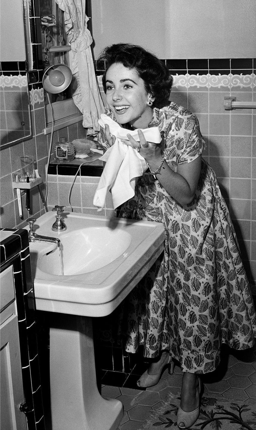 """<p>A young Elizabeth appears fresh faced after washing her face. According to <a href=""""https://www.hollywoodreporter.com/lists/12-elizabeth-taylor-s-red-carpet-beauty-secrets-1186451/item/she-never-wore-false-eyelashes-1186495"""" rel=""""nofollow noopener"""" target=""""_blank"""" data-ylk=""""slk:an interview with her former personal assistant"""" class=""""link rapid-noclick-resp"""">an interview with her former personal assistant</a>, Tim Mendelson, Elizabeth was a fan of drugstore brands and incorporated affordable creams like Jergens into her routine: """"She put cream on but she didn't use fancy brands,"""" he said.<br></p>"""