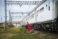 An employee walks down from a COVID-19 vaccination train parked at the Swartkops railroad yard outside Gqeberha, South Africa, Thursday Sept. 23, 2021. South Africa has sent a train carrying COVID-19 vaccines into one of its poorest provinces to get doses to areas where healthcare facilities are stretched. The vaccine train, named Transvaco, will go on a three-month tour through the Eastern Cape province and stop at seven stations for two weeks at a time to vaccinate people. (AP Photo/Jerome Delay)