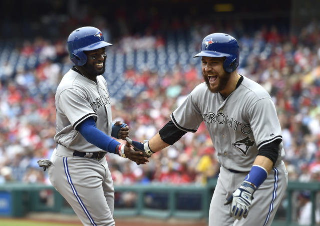 Toronto Blue Jays' Russell Martin, right, and Dwight Smith Jr. high-five after scoring on a Devon Travis double off Philadelphia Phillies' Nick Pivetta during the second inning of a baseball game, Sunday, May 27, 2018, in Philadelphia. (AP Photo/Derik Hamilton)