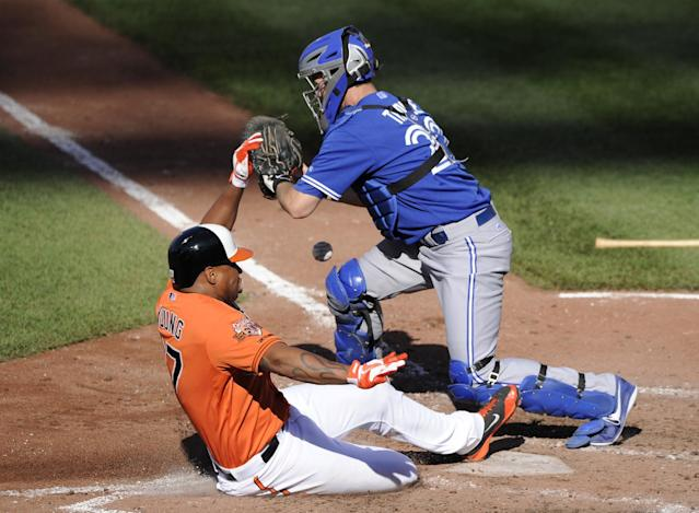 Baltimore Orioles' Delmon Young, left, slides home safely to score on a sacrifice fly by Nick Hundley, against Toronto Blue Jays catcher Josh Thole during the fourth inning of a baseball game Saturday, June 14, 2014, in Baltimore. (AP Photo/Nick Wass)