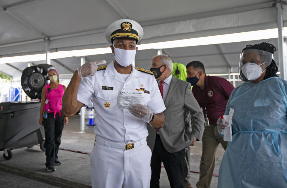 Vice Admiral Jerome Adams, the U.S. Surgeon General, speaks with the media alongside health care worker Varaiaia Barkus at the COVID-19 drive-thru testing center at Miami-Dade County Auditorium in Miami on Thursday, July 23, 2020. (David Santiago/Miami Herald/Tribune News Service via Getty Images)